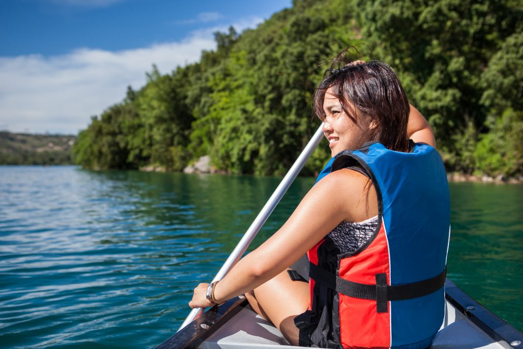A woman wearing a lifejacket sits at the front of a canoe while holding a paddle