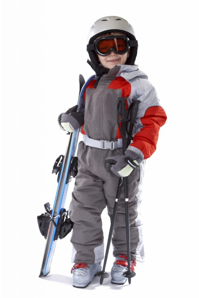 A child in a snowsuit with protective equipment ready to go skiing