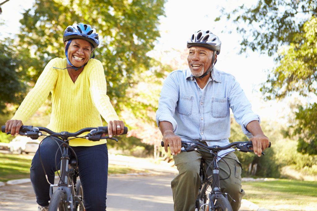 Two older adults smiling and wearing helmets while biking on a path