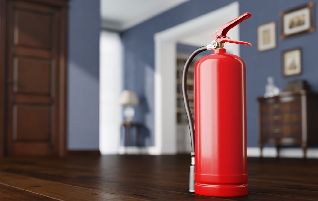 Close-up of a fire extinguisher sitting on the floor of an apartment