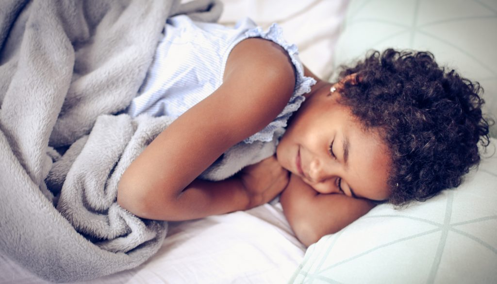 Close-up of a girl smiling while sleeping in a bed