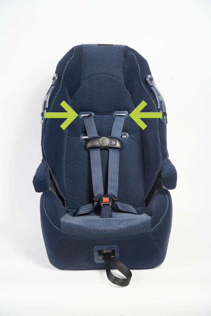 Green arrows point to the harness slots on the frame of a car seat