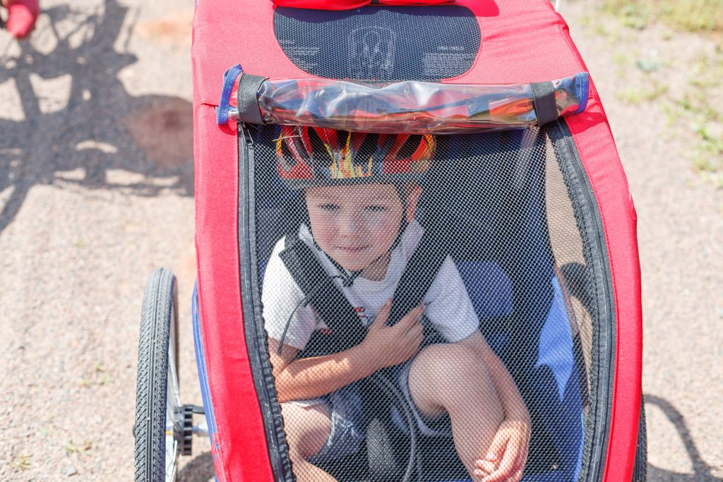 Child in bike trailer with helmet on